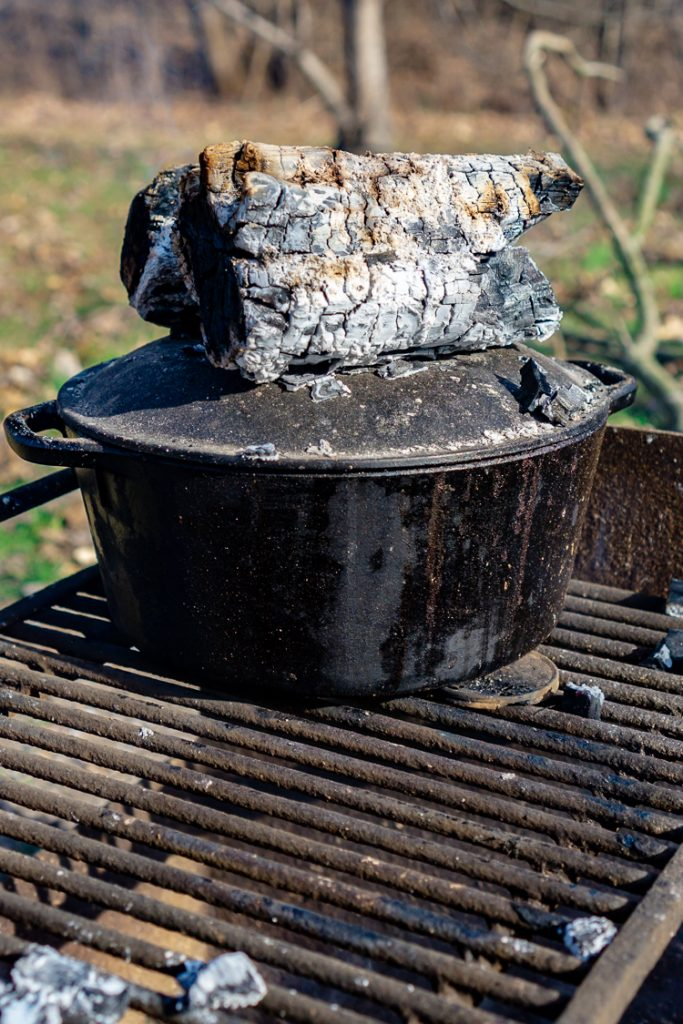 coals on top of dutch oven with homemade bread inside being baked over campfire